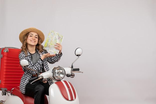 Lachende jonge vrouw op bromfiets met kaart op grijs