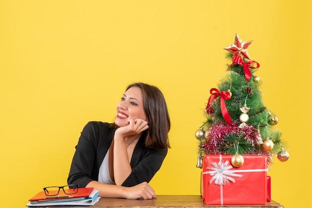 Lachende jonge vrouw op zoek naar iets zittend aan een tafel in de buurt van versierde kerstboom op kantoor op geel