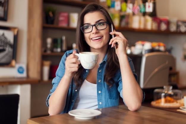 Lachende jonge vrouw praten via de mobiele telefoon in café