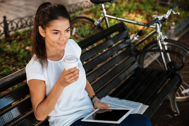 Lachende jonge vrouw rusten op de bank met kopje koffie in het stadspark en tablet te houden