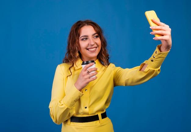 Lachende jonge vrouw selfie foto maken op smartphone op blauwe achtergrond.