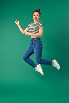 Lachende jonge vrouw springen in de lucht over groen.
