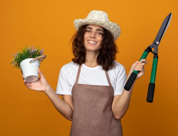 Lachende jonge vrouw tuinman in uniform dragen tuinieren hoed met bloem in bloempot met tondeuse geïsoleerd op oranje