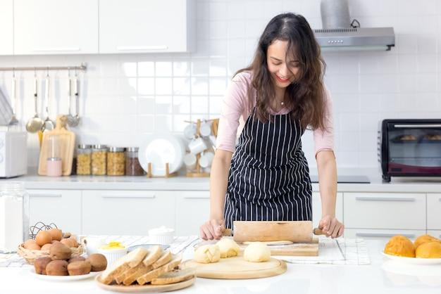 Lachende jonge vrouw werkt met houten roller pin maken van zoete taart of gebak deeg in de keuken, gelukkige duizendjarige vrouwelijke liefhebbende vrouw koken in schort familie diner of dessert bakken broodjes