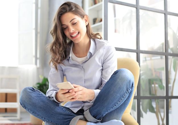 Lachende jonge vrouw zittend in de fauteuil in de woonkamer en met haar mobiele telefoon.
