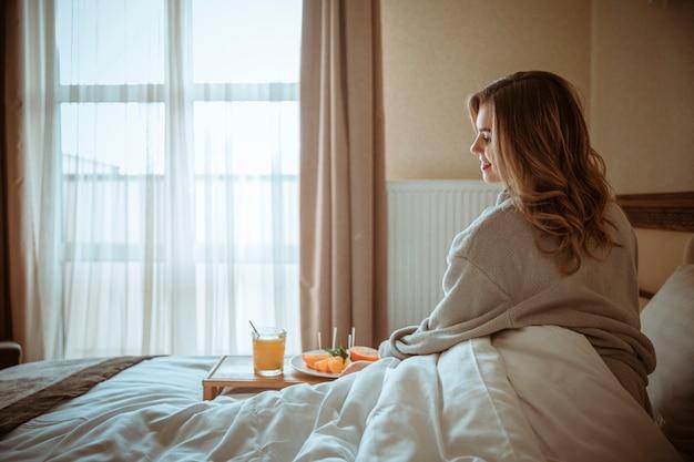Lachende jonge vrouw zittend op bed met gezond glas sap en fruit