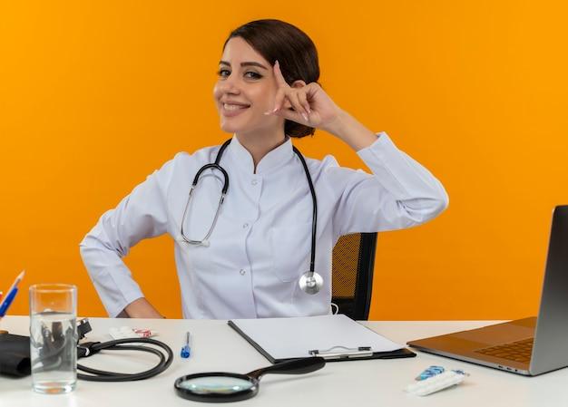 Lachende jonge vrouwelijke arts medische gewaad dragen met stethoscoop zit aan bureau werken op computer met medische hulpmiddelen vinger op voorhoofd op isolatie gele achtergrond
