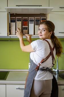 Lachende jonge vrouwelijke huisvrouw die zich voordeed tijdens algemene schoonmaak opruimen in de keuken van de kast