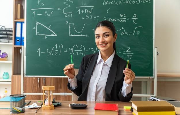 Lachende jonge vrouwelijke leraar zit aan tafel met schoolbenodigdheden met potlood in de klas