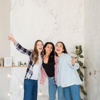 Lachende jonge vrouwen knuffelen