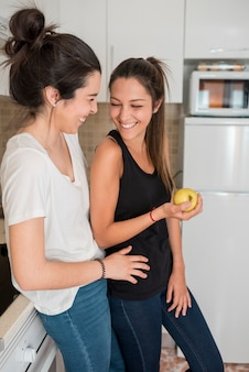 Lachende jonge vrouwenpaar die zich in keuken bevinden