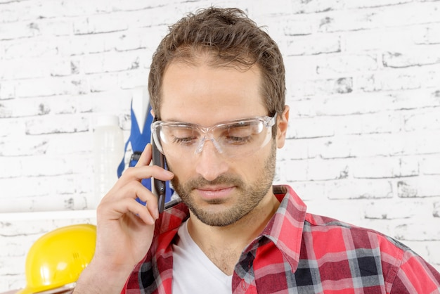 Lachende jonge werknemer telefoons in zijn atelier