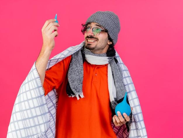 Lachende jonge zieke man met bril, muts en sjaal verpakt in geruite klysma's kijken naar kleintje geïsoleerd op roze muur met kopie ruimte