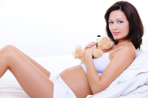 Lachende jonge zwangere vrouw omhelzen het teddy speelgoed