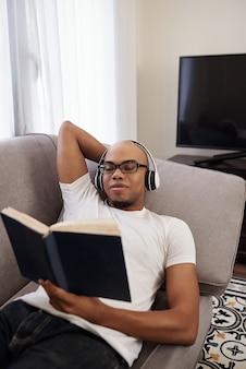 Lachende jonge zwarte man in koptelefoon ontspannen op de bank en interessante roman lezen