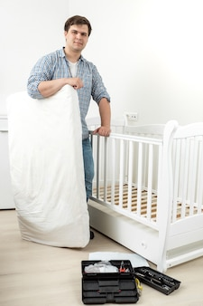 Lachende jongeman met matras op gedemonteerd babybedje