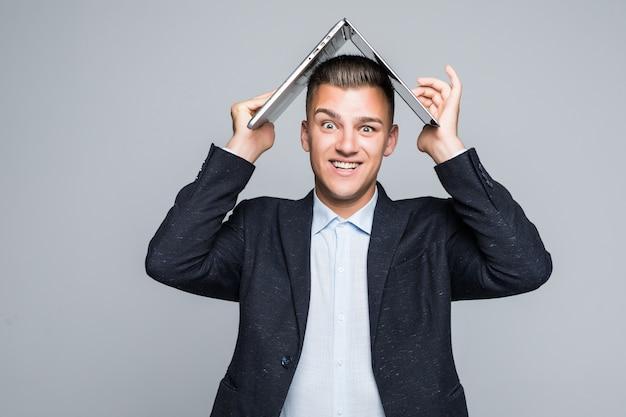 Lachende jongeman poseren met laptop op zijn hoofd gekleed in een donkere jas in studio geïsoleerd op een grijze muur