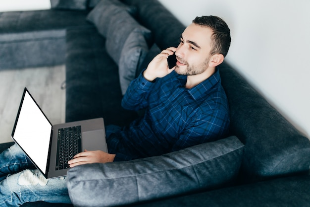 Lachende jongeman praten mobiele telefoon zittend op een bank thuis met laptopcomputer