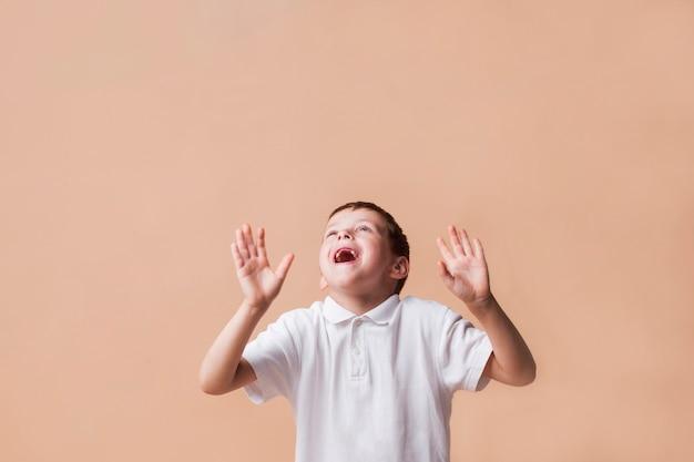 Lachende jongen die omhoog met hand kijkt die op beige achtergrond gesturing