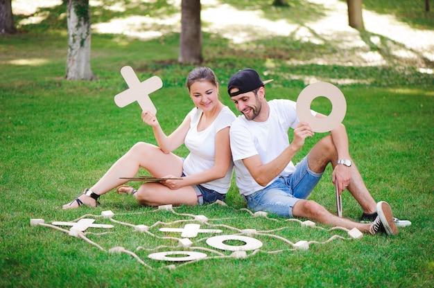 Lachende jongen en meisje tic-tac-toe spelen in het park.