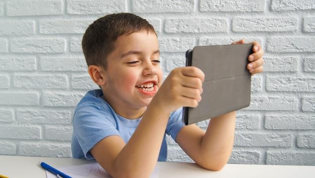 Lachende jongen gebruikt laptop en communiceert thuis op internet