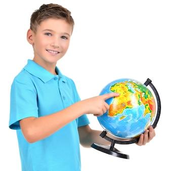 Lachende jongen in casual bedrijf wereldbol met in handen en punten erop - geïsoleerd op wit
