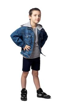 Lachende jongen in een spijkerjasje houdt handen aan de zijkanten op een witte geïsoleerde achtergrond