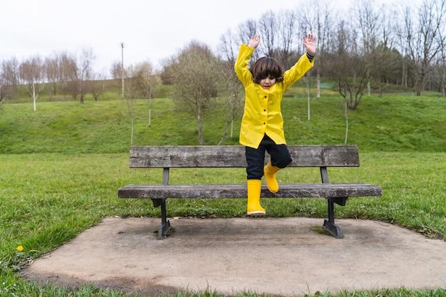 Lachende jongen in regenjas en gele regenlaarzen springen met open armen van een bankje op een parkpad