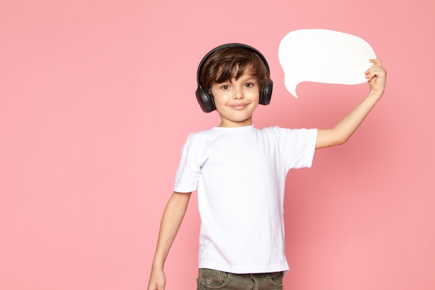 Lachende jongen in wit t-shirt en kaki jeans in zwarte koptelefoon luisteren naar muziek en tekstballon