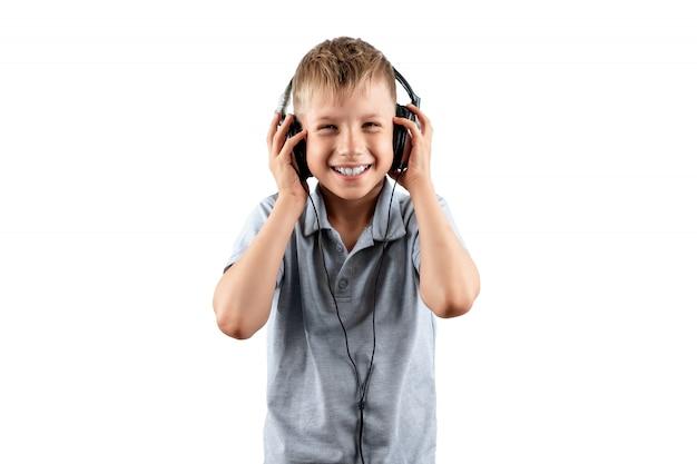 Lachende jongen luistert naar muziek in grote koptelefoon geïsoleerd op een witte achtergrond