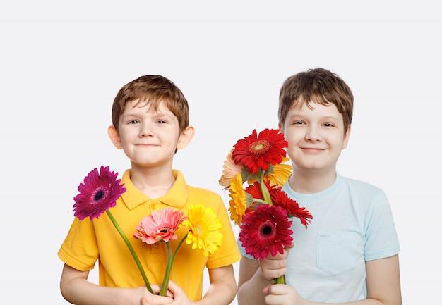 Lachende jongen met boeketgerberabloemen.