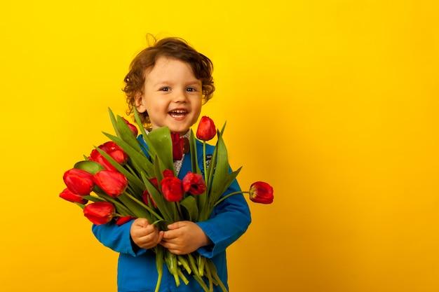 Lachende jongen met een boeket van rode tulpen. moederdag,