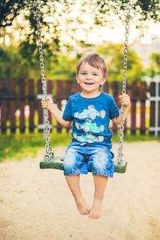 Lachende jongen op een schommel