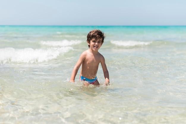 Lachende jongen spelen in water aan de kust