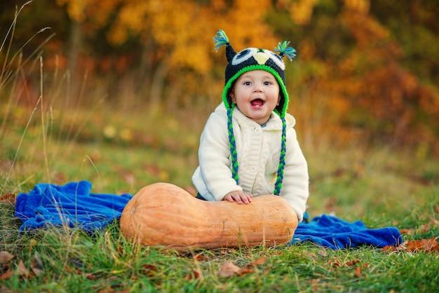 Lachende jongetje met twee tanden in een gebreide muts en warme stijlvolle kleding zittend op blauwe plaid op het gras met pompoen en herfst bomen op achtergrond