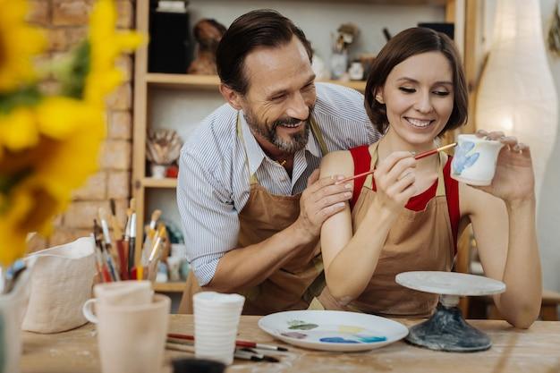 Lachende keramisten. paar ervaren keramisten lachen hardop terwijl ze een grapje maken tijdens het werk
