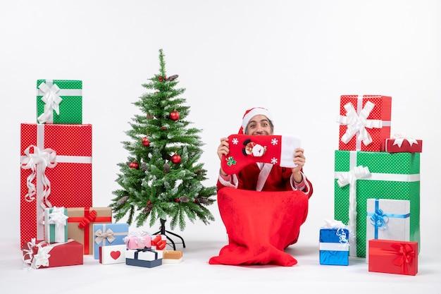 Lachende kerstman zittend op de grond en kerst sok verhogen naar zijn gezicht in de buurt van geschenken en versierde nieuwe jaarboom op witte achtergrond