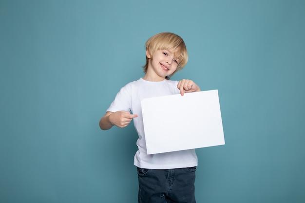 Lachende kind jongen in wit t-shirt en spijkerbroek met een leeg stuk papier op blauw