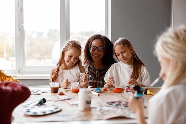 Lachende kinderen die kunst maken met aquarelverf
