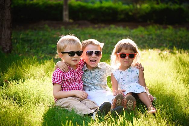 Lachende kinderen in de tuin in zonnebril