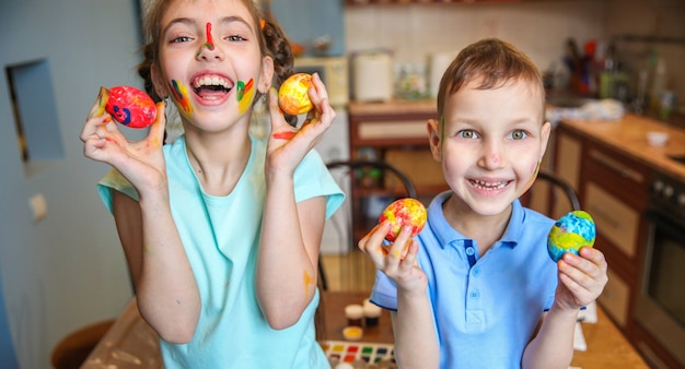 Lachende kinderen jongen en meisje tonen versierde paaseieren thuis in de keuken
