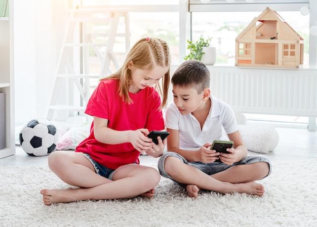 Lachende kinderen kijken naar smartphone