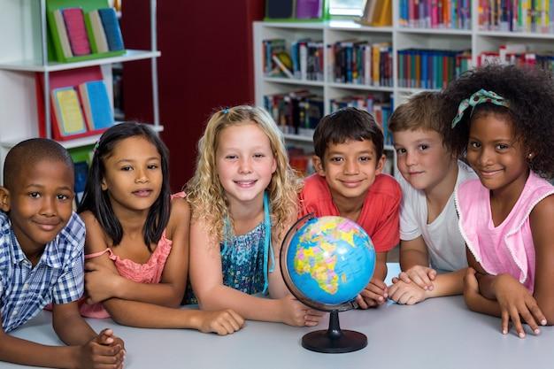 Lachende kinderen met globe op tafel