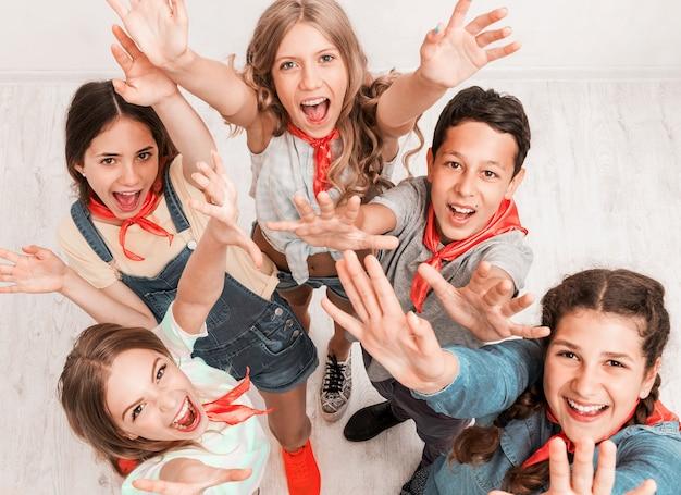 Lachende kinderen met omhoog handen
