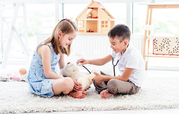 Lachende kinderen spelen arts met teddybeer in lichte kamer