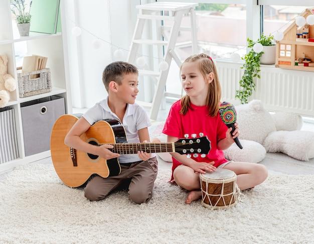 Lachende kinderen spelen op drum en gitaar