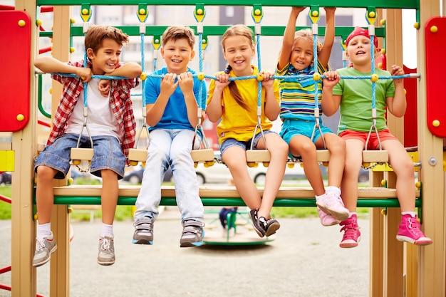 Lachende klasgenoten zitten in een rij op de speelplaats