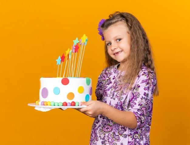 Lachende kleine blonde meisje met verjaardagstaart geïsoleerd op oranje muur met kopie ruimte