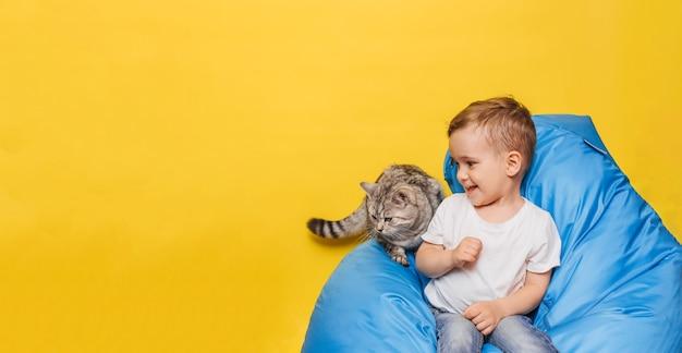 Lachende kleine jongen op geel zit met een kat op een blauwe stoel