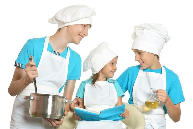 Lachende kleine kinderen in chef-kok uniformen poseren op witte achtergrond